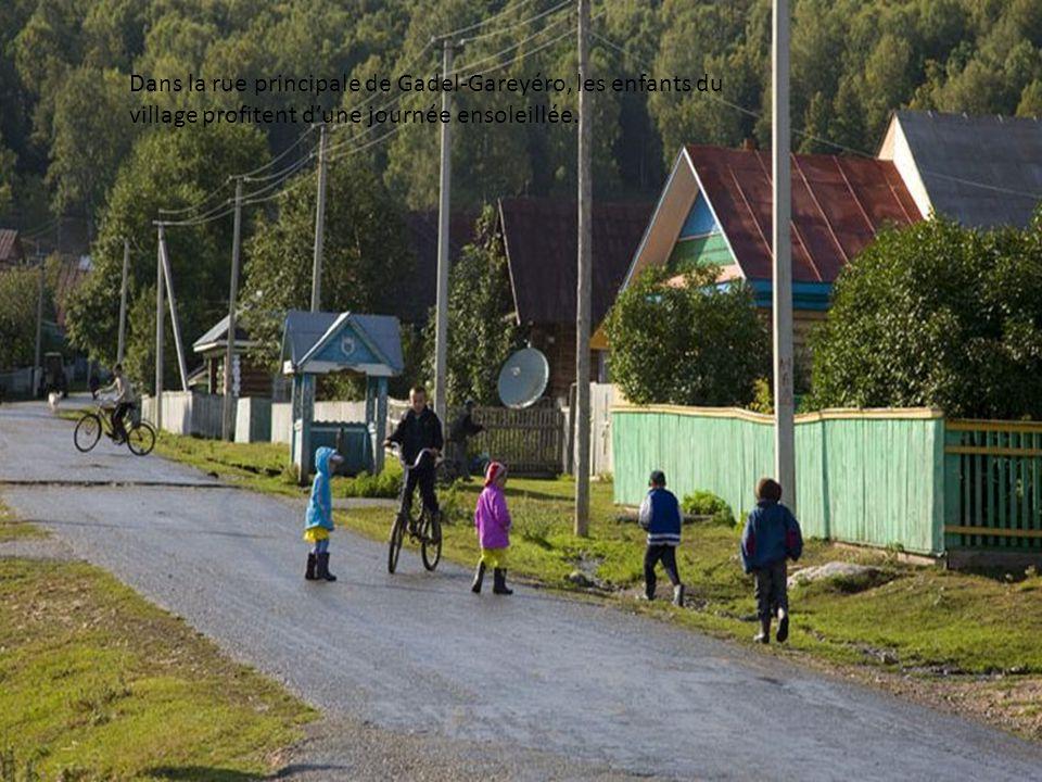 Dans la rue principale de Gadel-Gareyéro, les enfants du village à vélo samusent devant les oies qui se chauffent au soleil