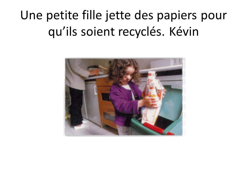 Une petite fille jette des papiers pour quils soient recyclés. Kévin