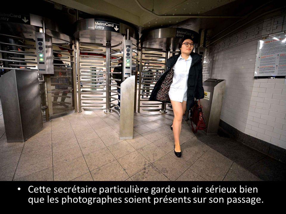 Cette secrétaire particulière garde un air sérieux bien que les photographes soient présents sur son passage.