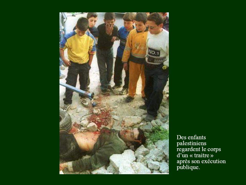 Des enfants palestiniens regardent le corps d'un « traitre » après son exécution publique.
