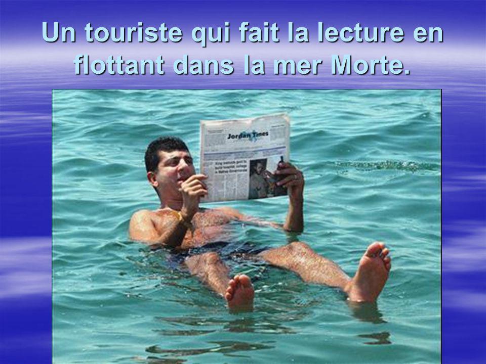 Un touriste qui fait la lecture en flottant dans la mer Morte.