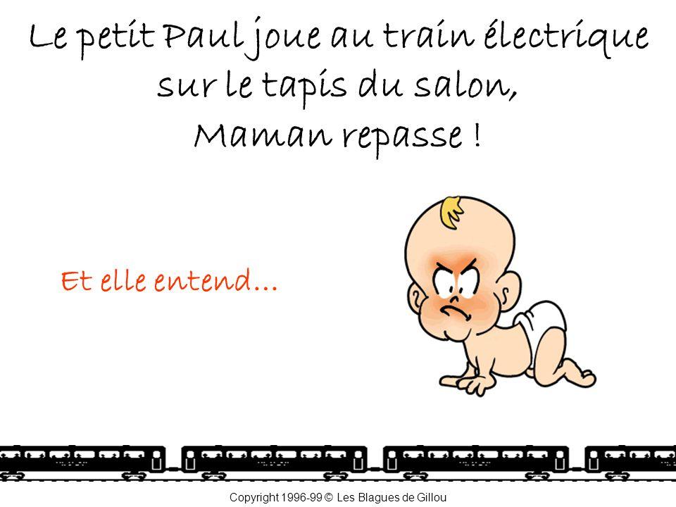 Le petit Paul joue au train électrique sur le tapis du salon, Maman repasse .
