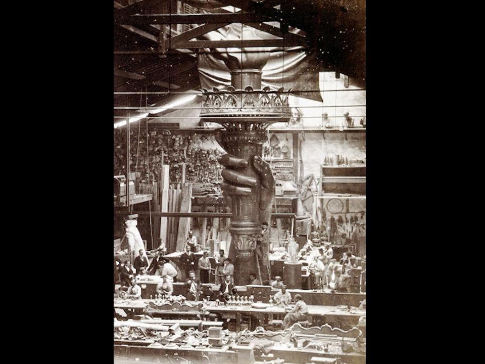 Ouvriers construisant la Statue de la Liberté dans l`entrepôt d`un atelier parisien de Bartholdi; premier modèle : main gauche; et un quart de la tête