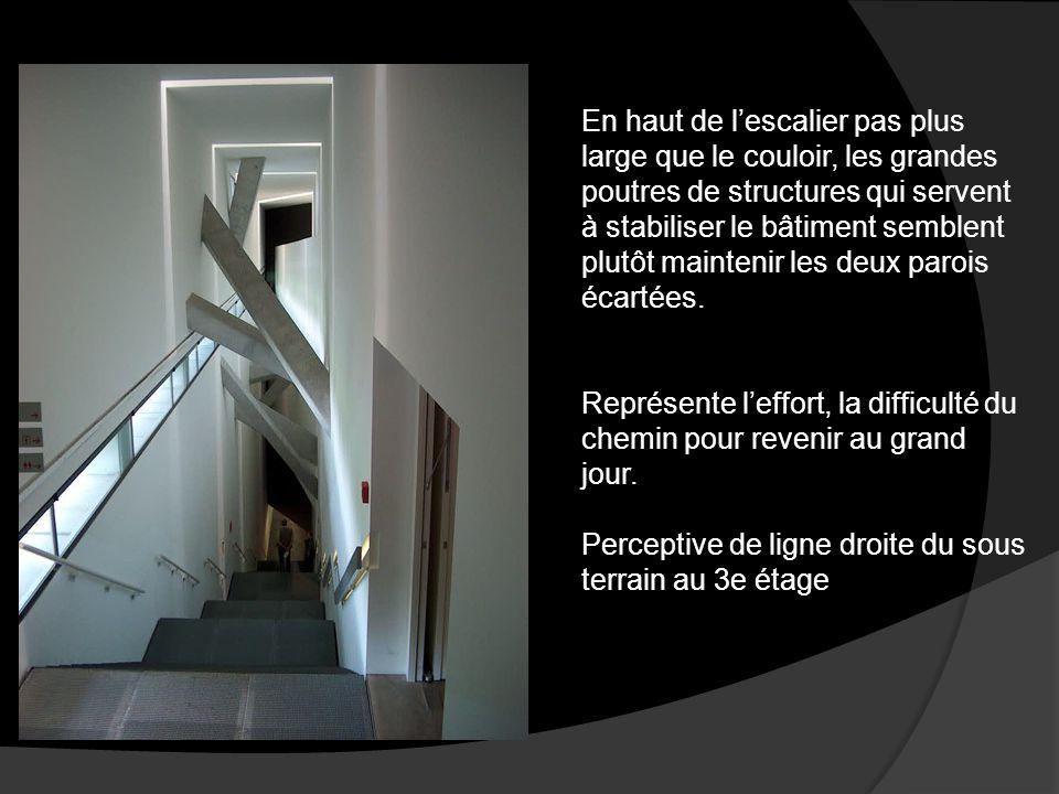 En haut de l'escalier pas plus large que le couloir, les grandes poutres de structures qui servent à stabiliser le bâtiment semblent plutôt maintenir