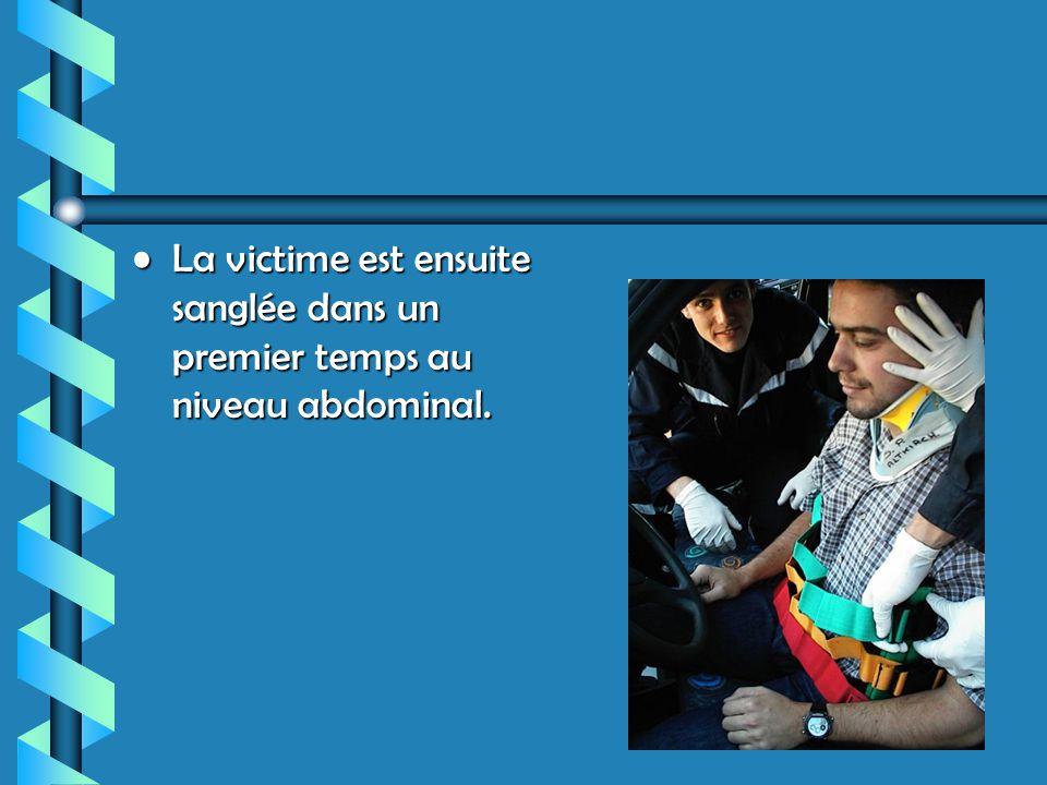 La victime est ensuite sanglée dans un premier temps au niveau abdominal.La victime est ensuite sanglée dans un premier temps au niveau abdominal.