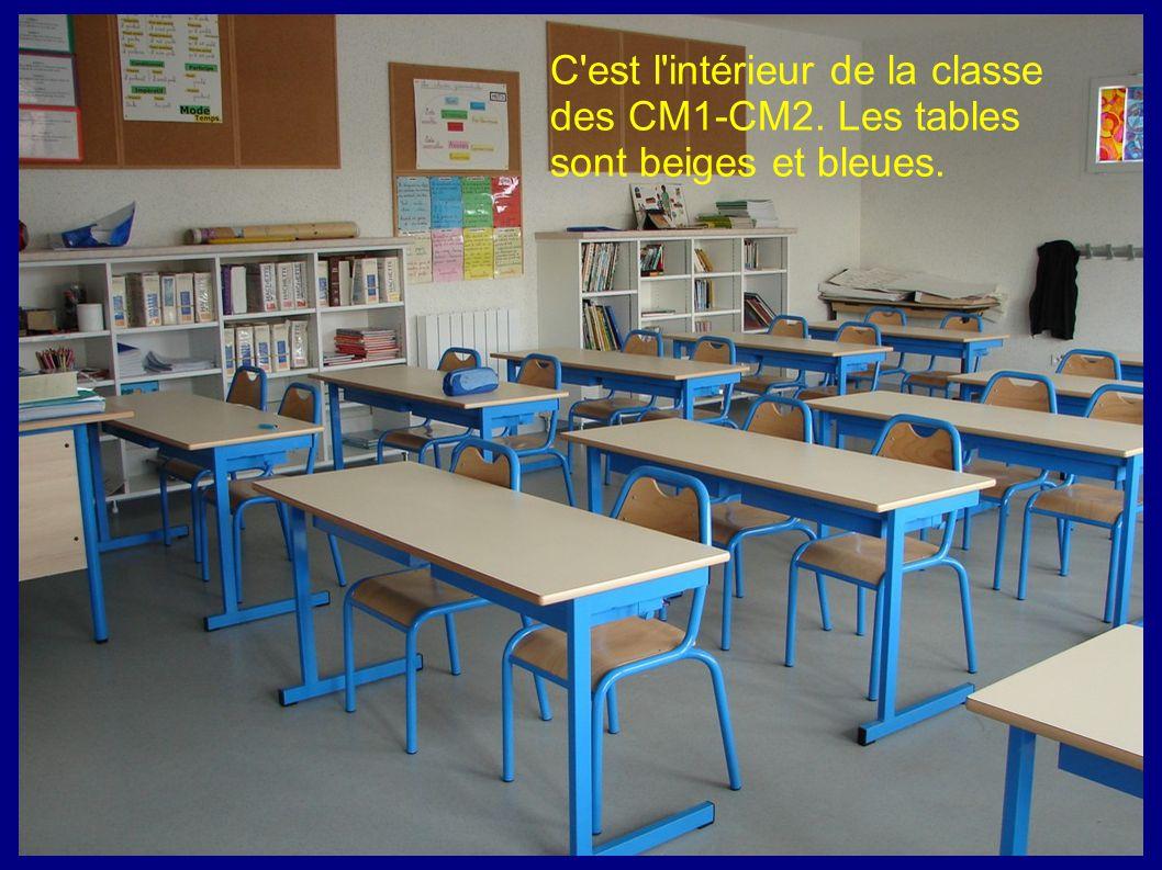 C'est l'intérieur de la classe des CM1-CM2. Les tables sont beiges et bleues.
