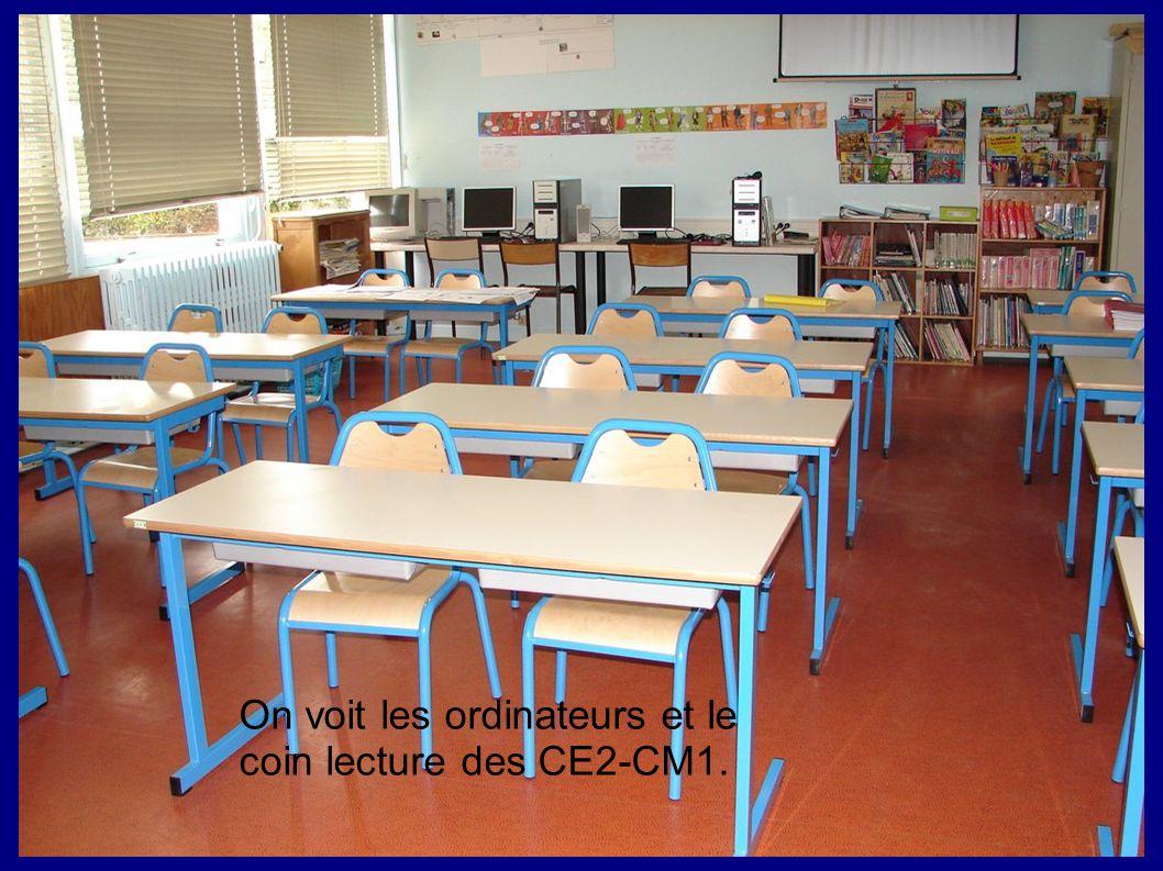 On voit les ordinateurs et le coin lecture des CE2-CM1.