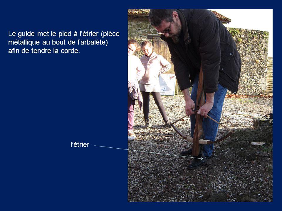Le guide met le pied à l'étrier (pièce métallique au bout de l'arbalète) afin de tendre la corde. l'étrier