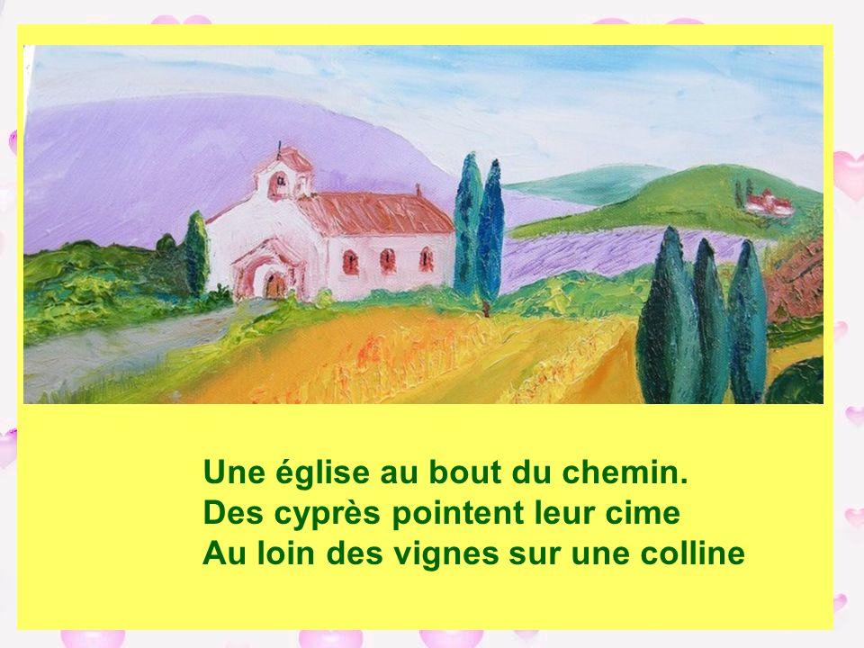 Une église au bout du chemin. Des cyprès pointent leur cime Au loin des vignes sur une colline