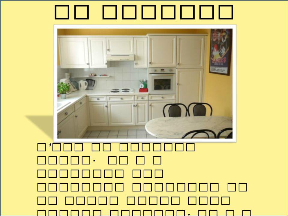 C ' est la cuisine jaune. Il y a beaucoup des placards blanches et un petit table avec quatre chaises. Il y a un beau poster. Le four est à droite de
