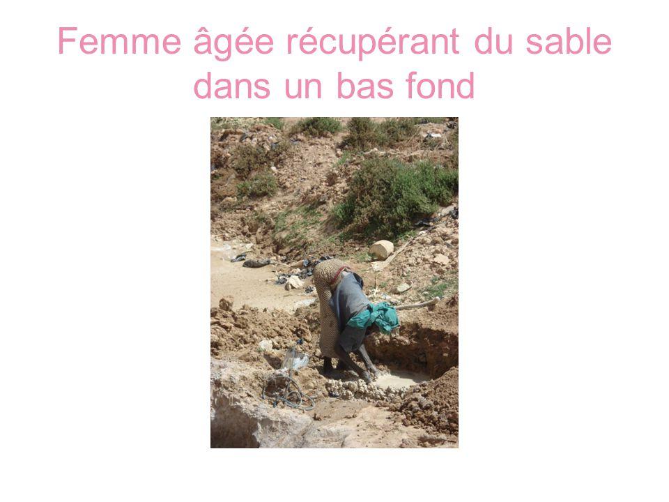 Femme âgée récupérant du sable dans un bas fond
