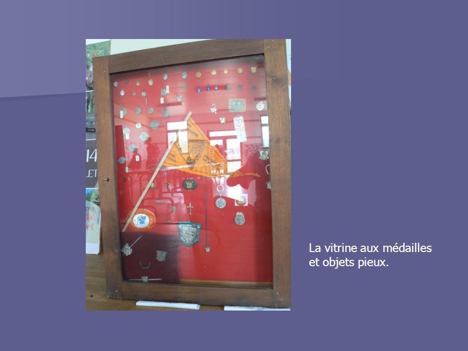 La vitrine aux médailles et objets pieux.