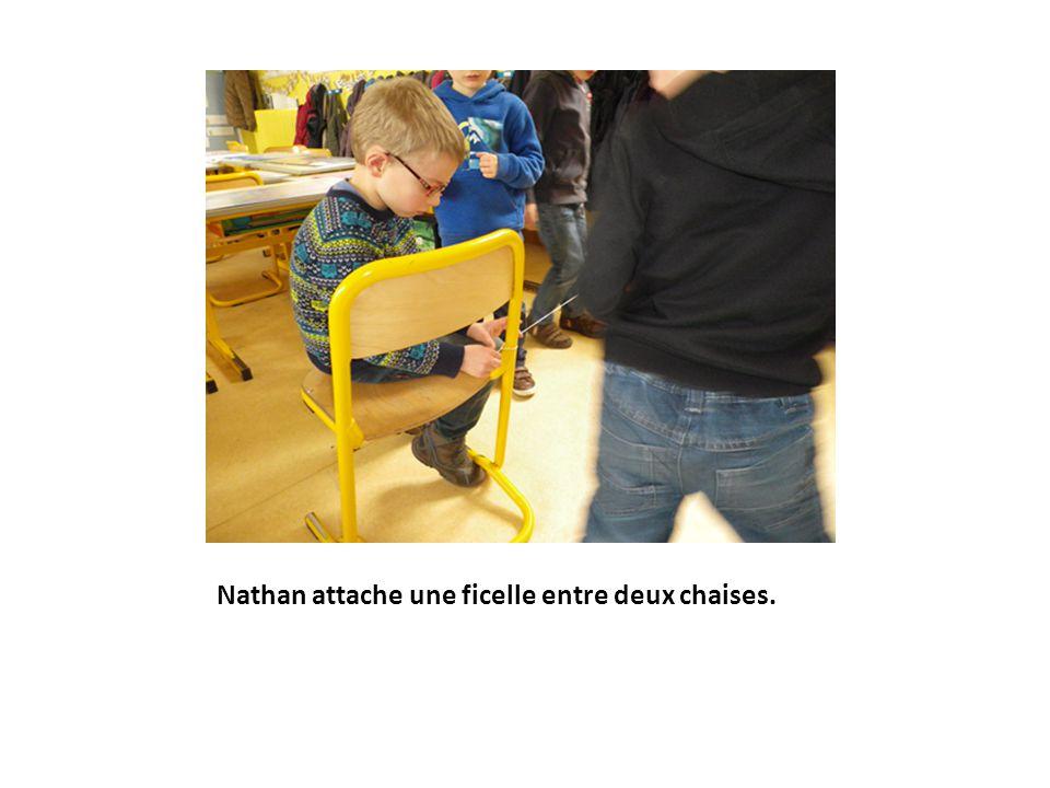 Nathan attache une ficelle entre deux chaises.
