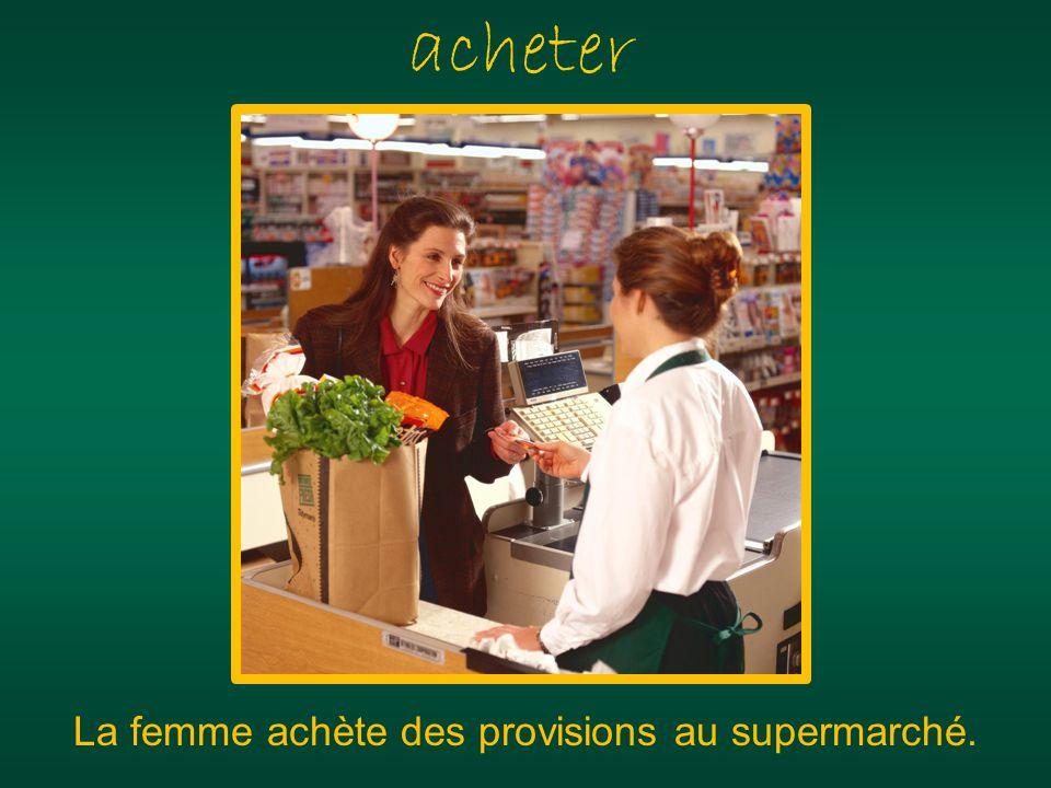 acheter La femme achète des provisions au supermarché.