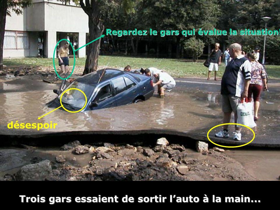 Trois gars essaient de sortir l'auto à la main... désespoir Regardez le gars qui évalue la situation!
