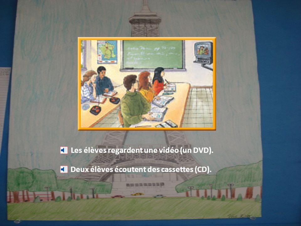 Les élèves regardent une vidéo (un DVD). Deux élèves écoutent des cassettes (CD).