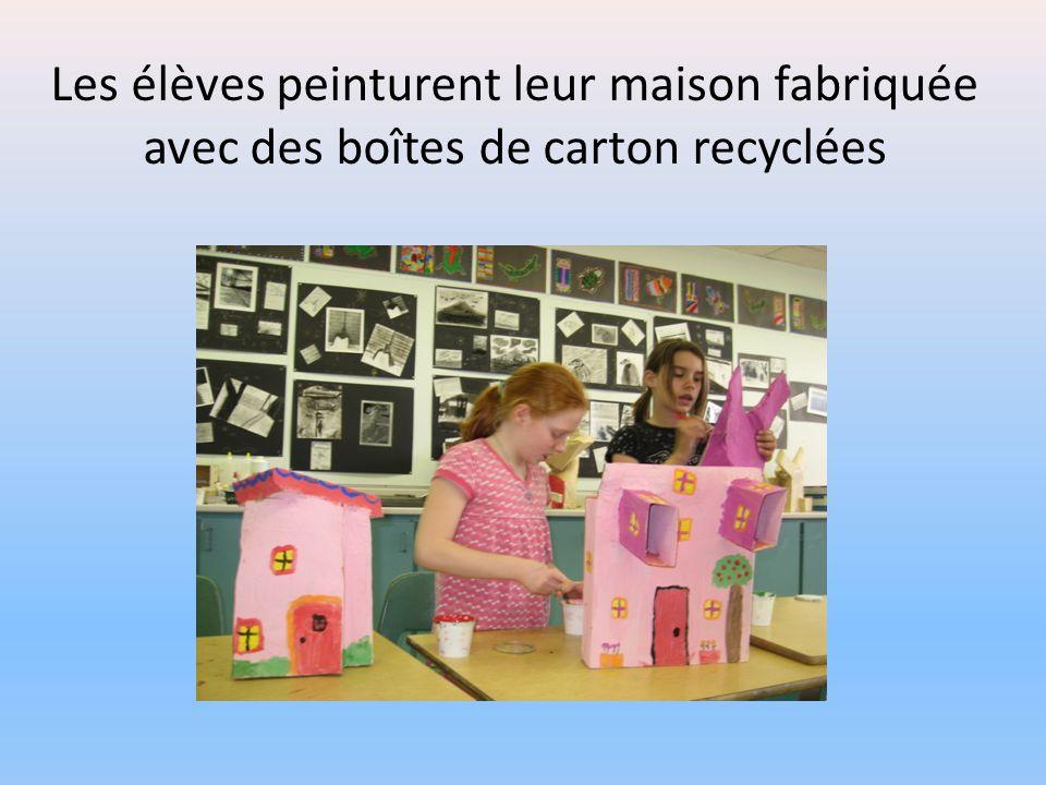 Les élèves peinturent leur maison fabriquée avec des boîtes de carton recyclées