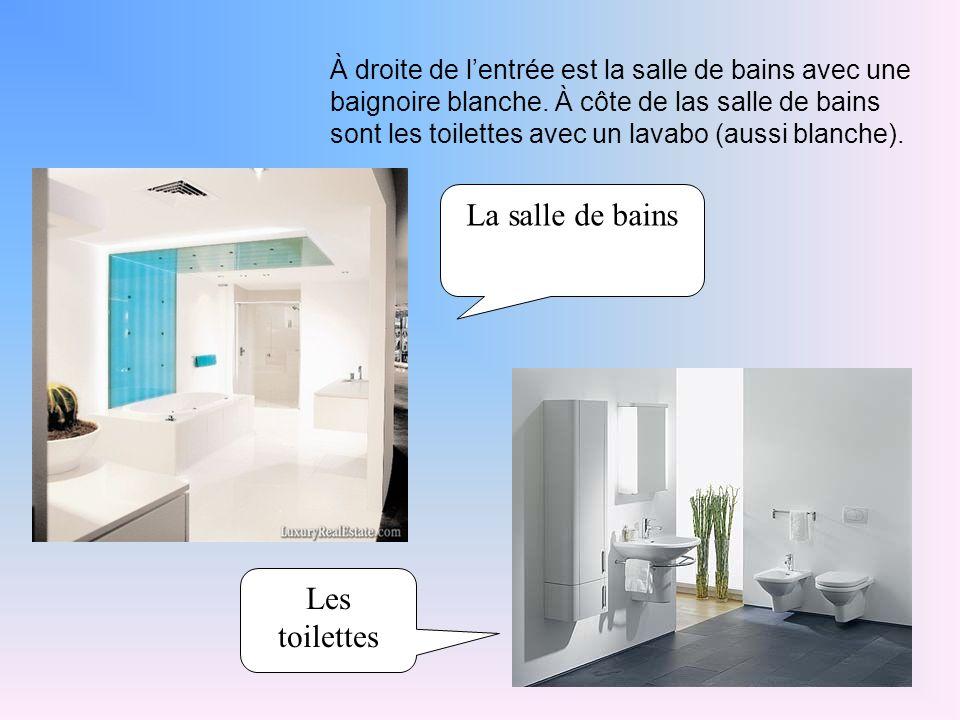 À droite de l'entrée est la salle de bains avec une baignoire blanche.