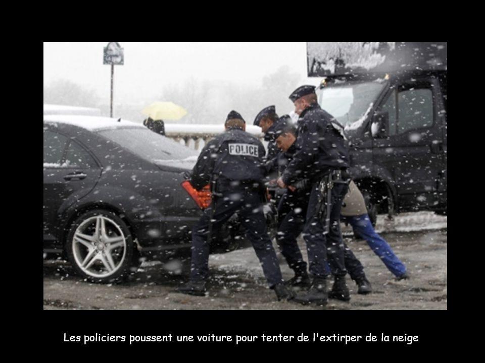 Les policiers poussent une voiture pour tenter de l extirper de la neige.