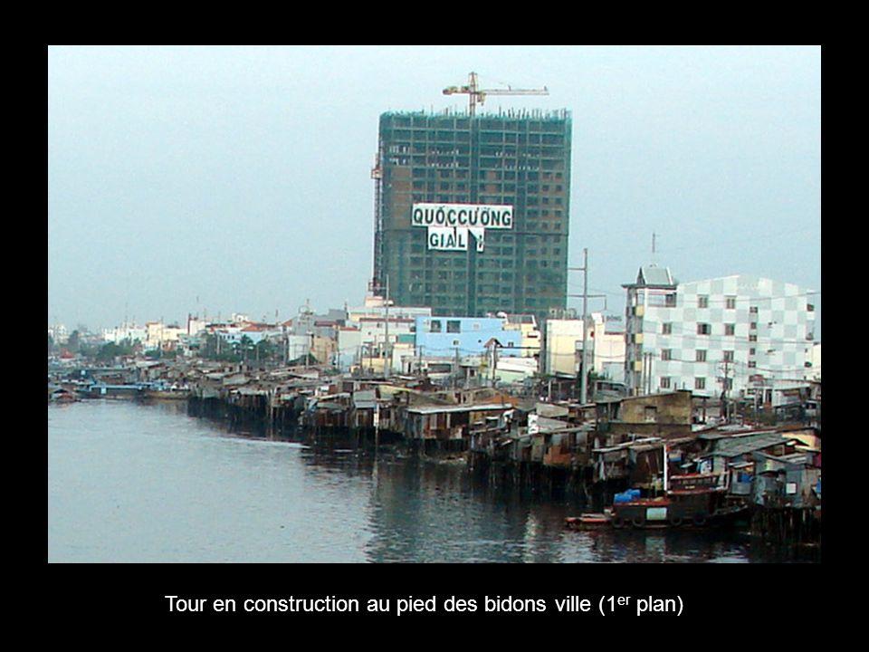 Tour en construction au pied des bidons ville (1 er plan)