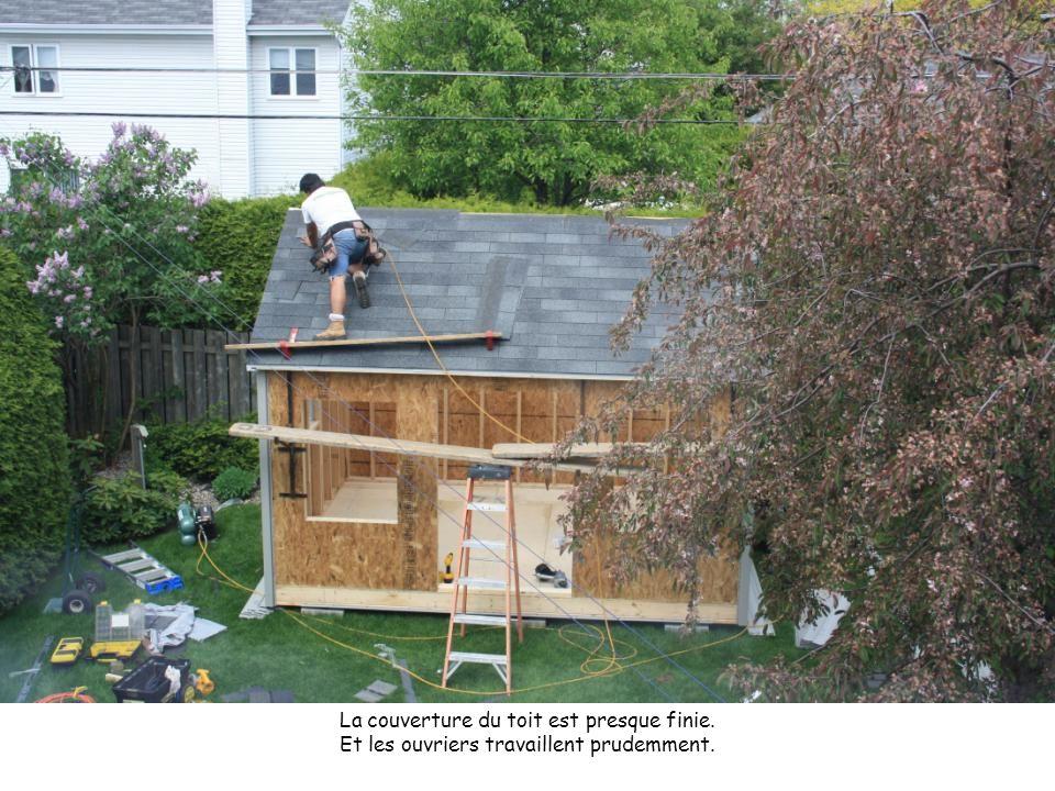 La couverture du toit est presque finie. Et les ouvriers travaillent prudemment.