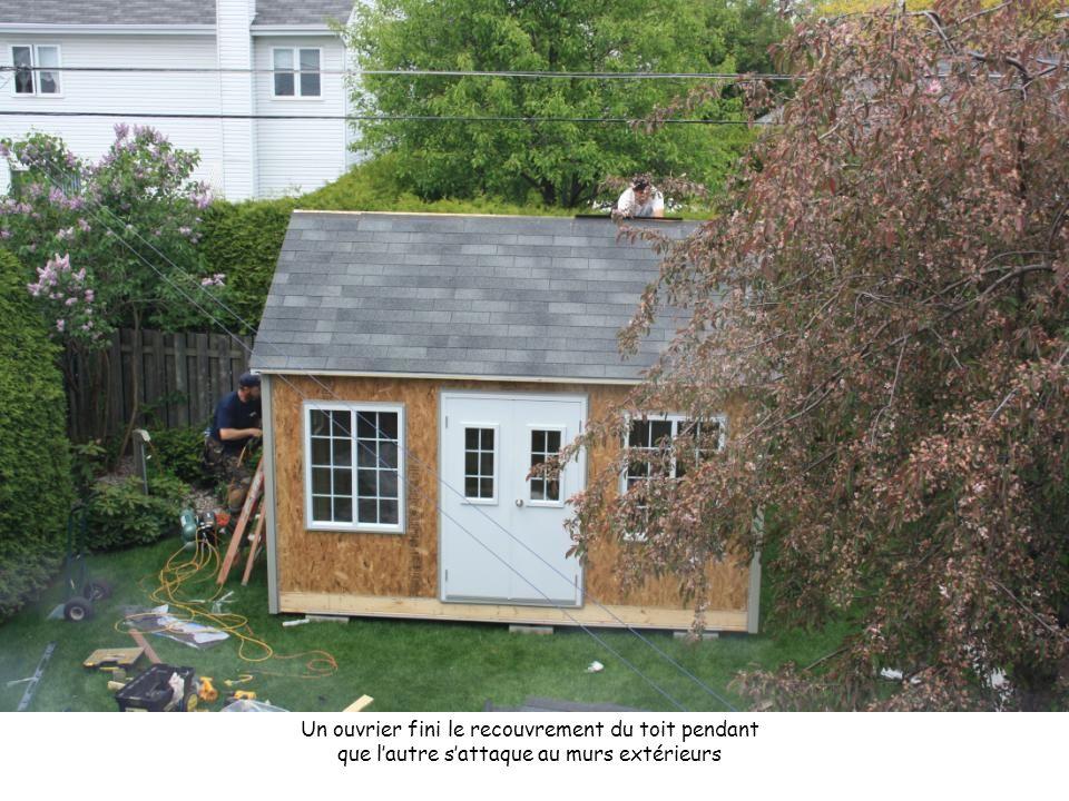 Un ouvrier fini le recouvrement du toit pendant que l'autre s'attaque au murs extérieurs