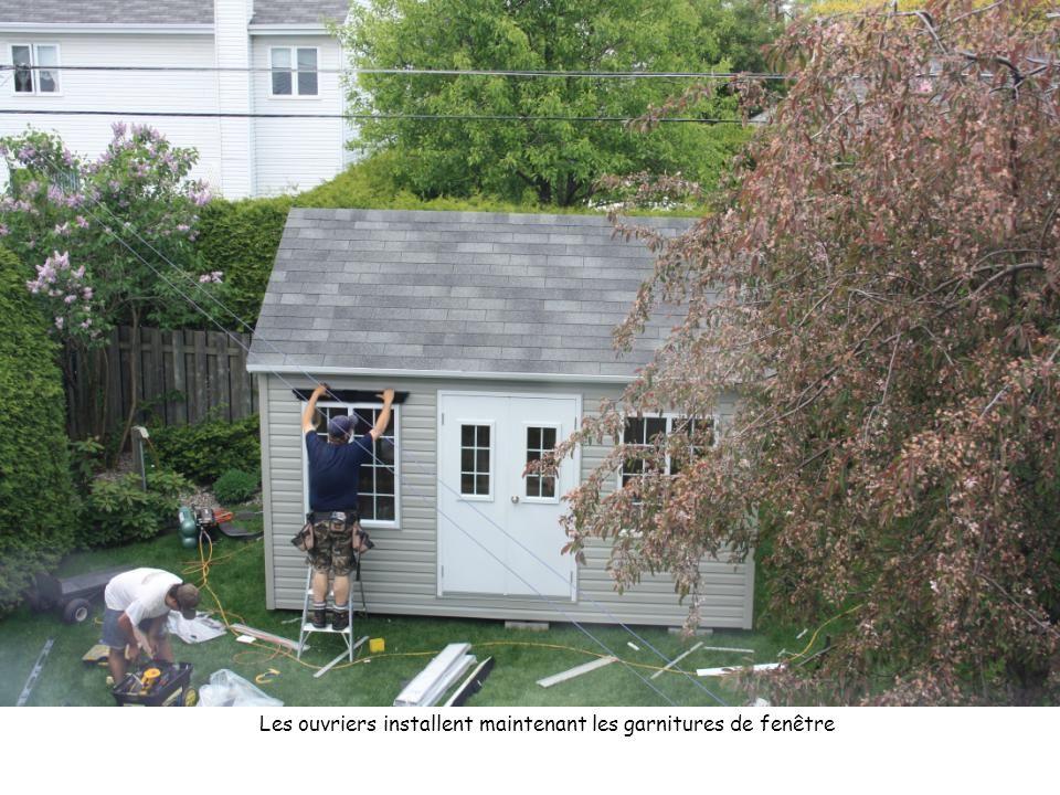 Les ouvriers installent maintenant les garnitures de fenêtre