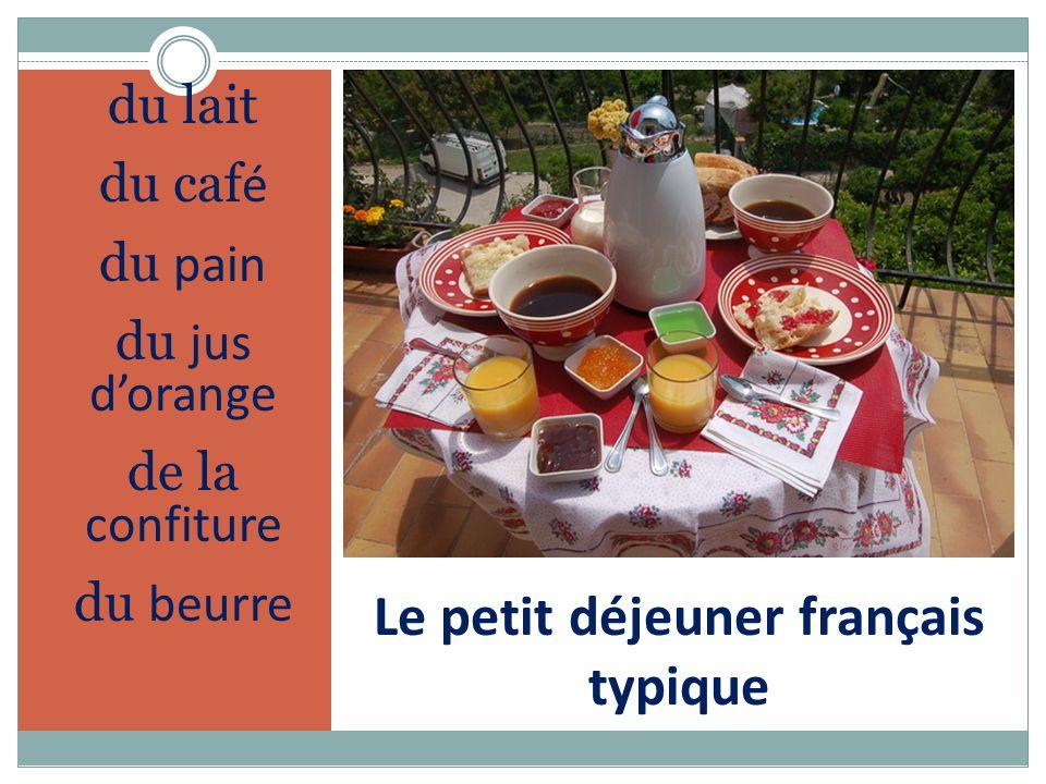 Le petit déjeuner français typique du lait du caf é du pain du jus d'orange de la confiture du beurre